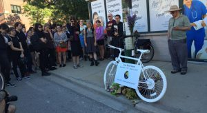 People gather in memorial around a ghost bike to show their respects.