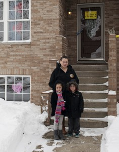 Jessica Loy stands outside her new home with her two youngest children, twins Carla and Carlos, Jr. (Lizz Giordano/Medill)