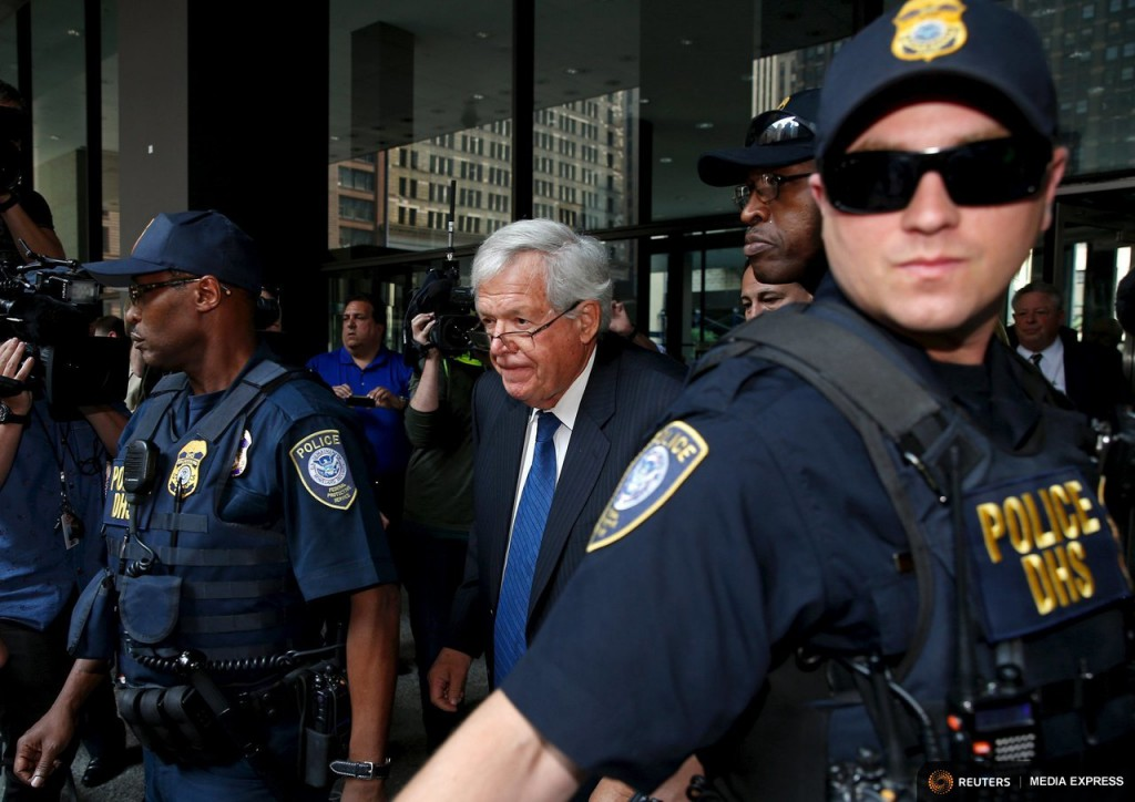 Former U.S. House of Representatives Speaker Dennis Hastert is surrounded by officers as he leaves federal court after pleading not guilty to federal charges of trying to hide large cash transactions and lying to the FBI in Chicago