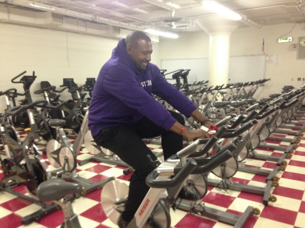 Bates hops on a bike while giving a tour of the athletic facilities. He has stayed active since his NFL retirement. (Maddie Lee/Medill)