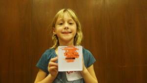"Eve Rothbaum, 9, holding her tzedakah box, said she will feed her ""kitty"" everyday with coins. (Yingxu Jane Hao/Medill)"