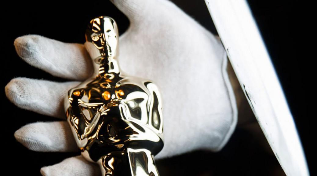 a hand holding an oscar statue