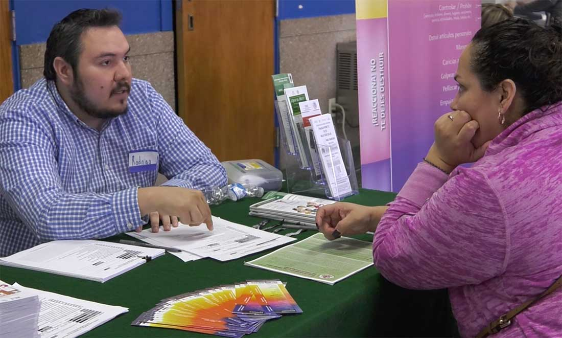 Rodrigo Vences, employee at the Honorary Consulate of Mexico in Chicago, explaining citizenship process with prospective applicant.