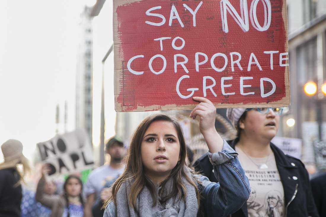 "Woman with ""No to corporate greed"" sign"