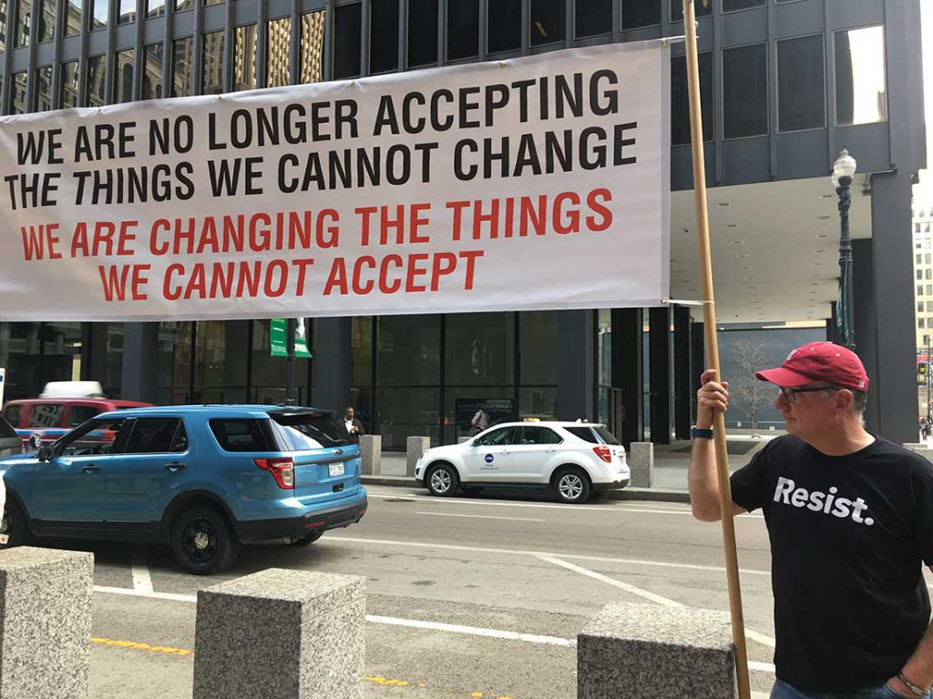 """Chicago native Jim Coleman holds a banner at the fifth """"Resist Trump Tuesdays"""" march"""