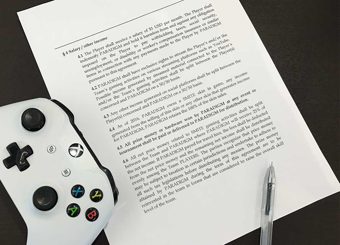 Photo of a pen, an Xbox One controller and a copy of an e-sports player contract.