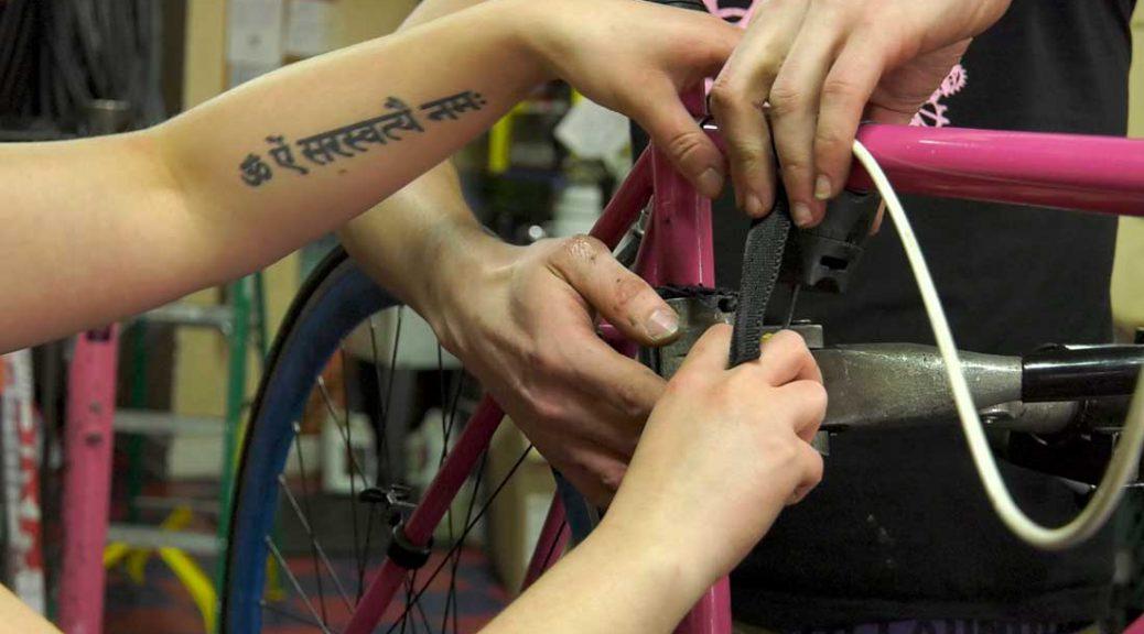 People repair a bike together