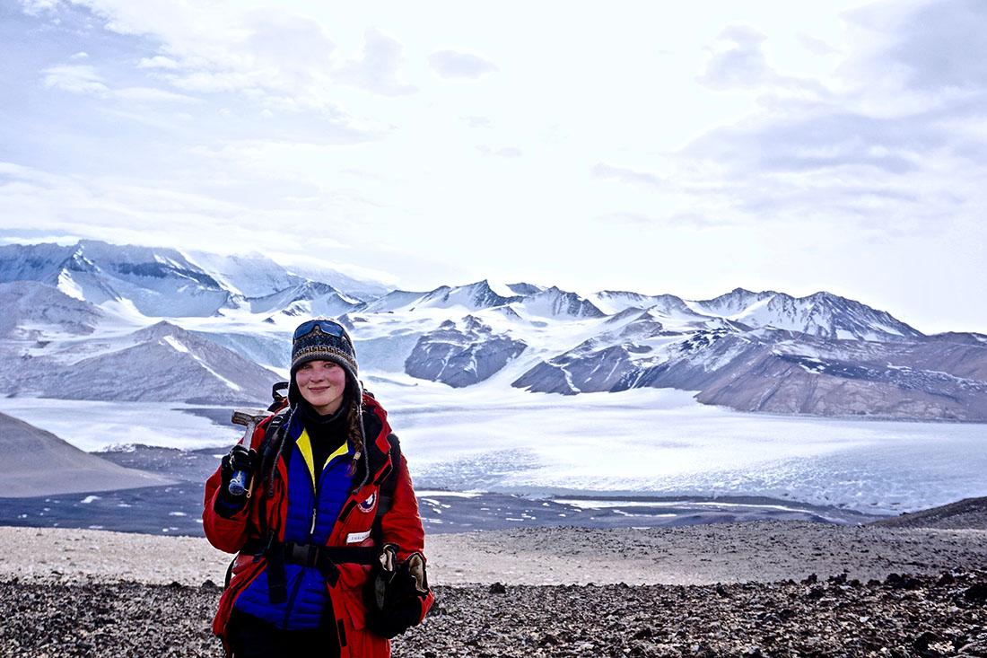 Laura Mattas stands before miles of Antarctic glaciers.