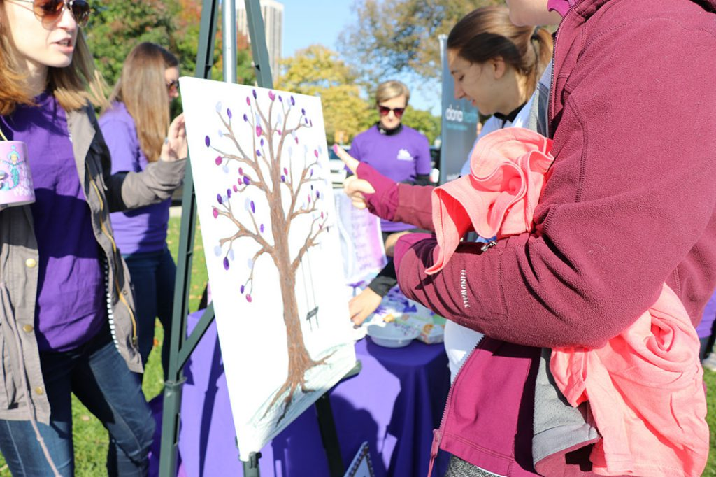 """Treatment centers set up booths throughout the walk with both information and activities. The Renfrew Center of Northbrook, Illinois asked survivors to add their purple thumbprint """"leaves"""" on a tree. Purple is considered the official ribbon color for eating disorder awareness. (Colleen Zewe/MEDILL)"""