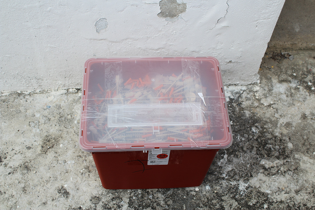 A bio-hazard box full of used needles, sits ready for disposal.