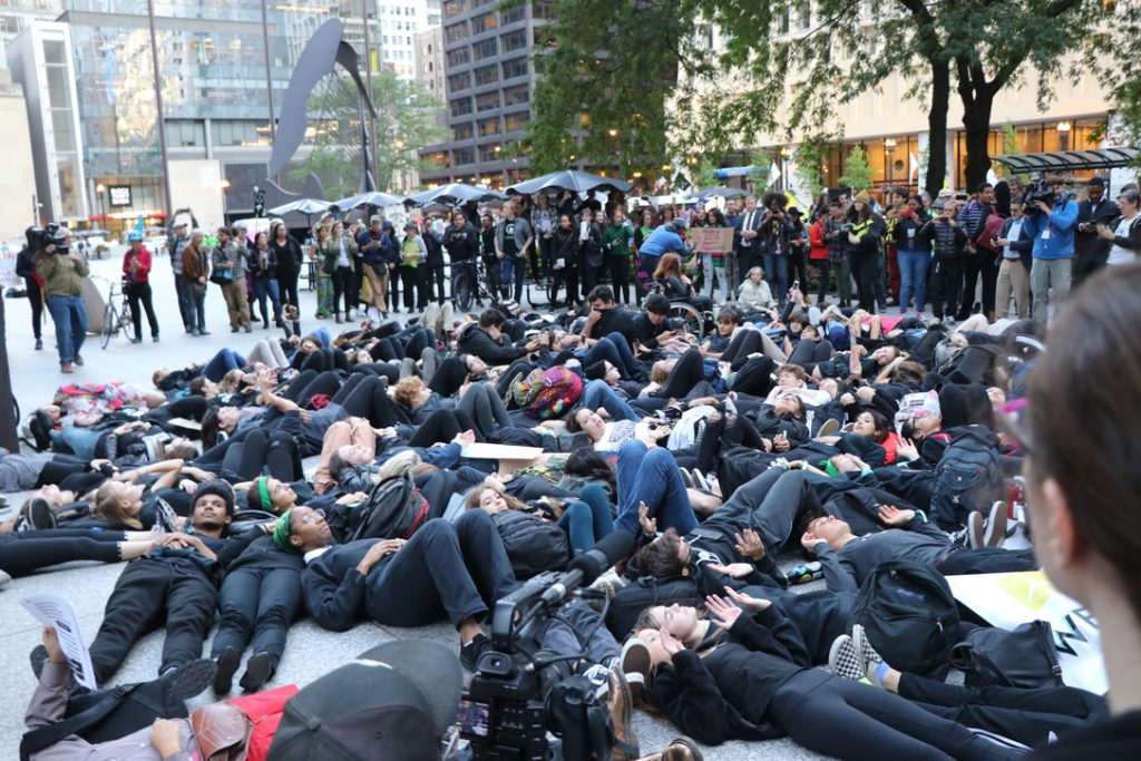"Youth Climate Strike activists participate in a ""die-in"" outside Chicago City Hall in Daley Plaza. (Zack Fishman/MEDILL)"